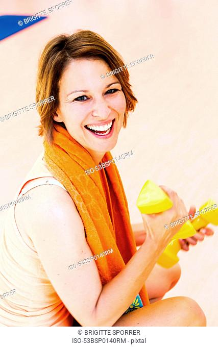 Smiling woman lifting weights outdoors