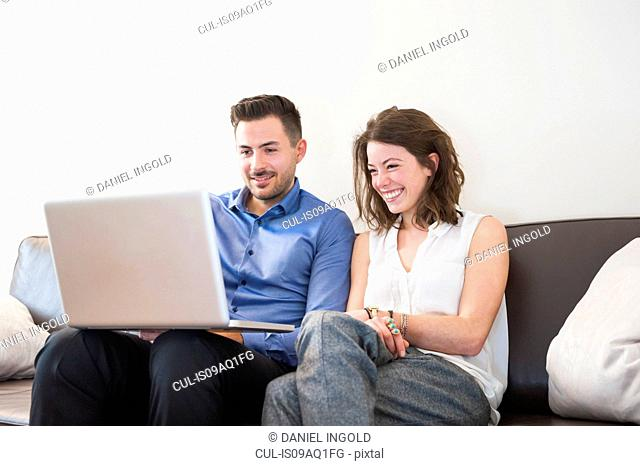 Young couple sitting on sofa looking at laptop