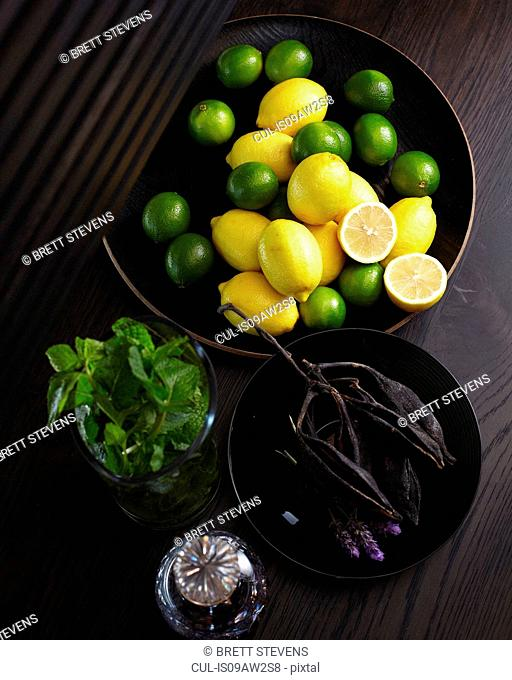 Overhead view of lemons and limes in bowl with jar of mint