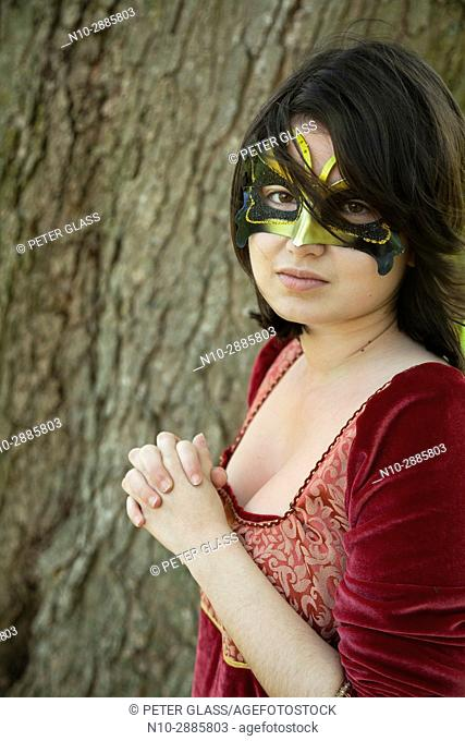 Young woman, standing by a tree in a park, wearing a mask and red vintage dress