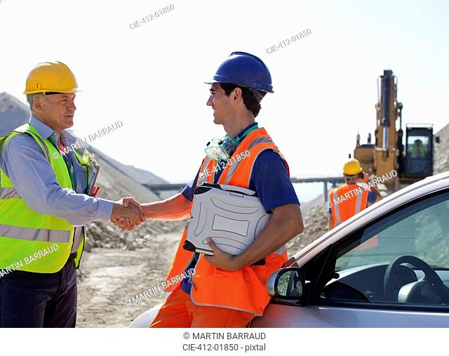Worker and businessman shaking hands in quarry
