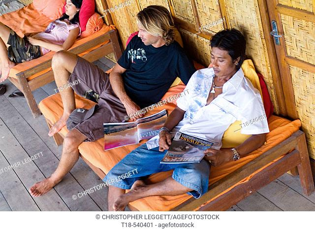 two young men and woman relaxing on bench