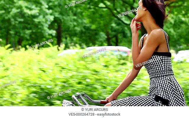 Gorgeous young woman smiling at you while cycling along a country road under trees on a summer day