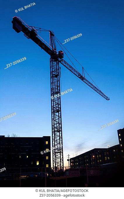Pink lights, symbolic of women's issues, mark a tall crane towering over a breast cancer center being built in Ontario, Canada
