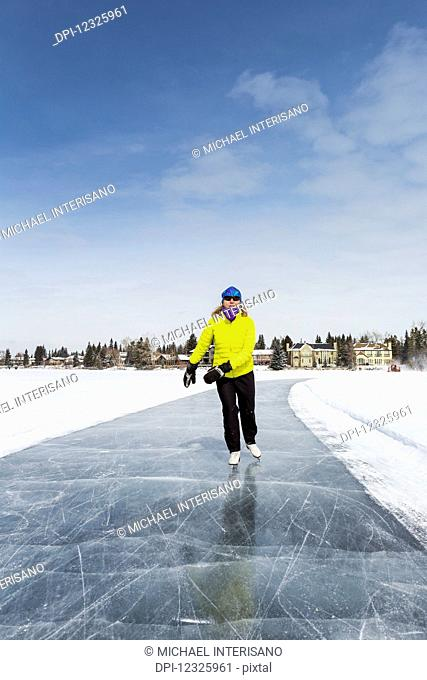 Woman skating on freshly groomed ice on lake with houses in the background and blue sky; Calgary, Alberta, Canada