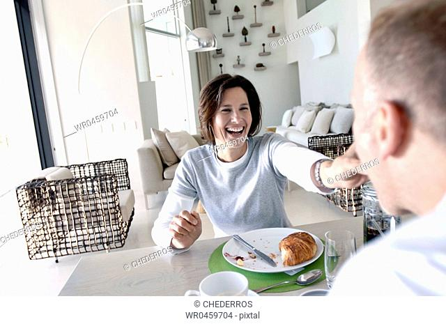 Mature woman feeding her husband and laughing
