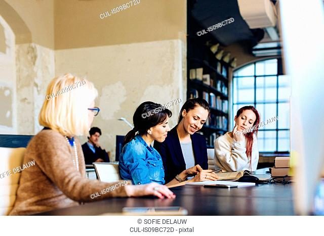Four businesswomen sitting at desk in office, looking through book
