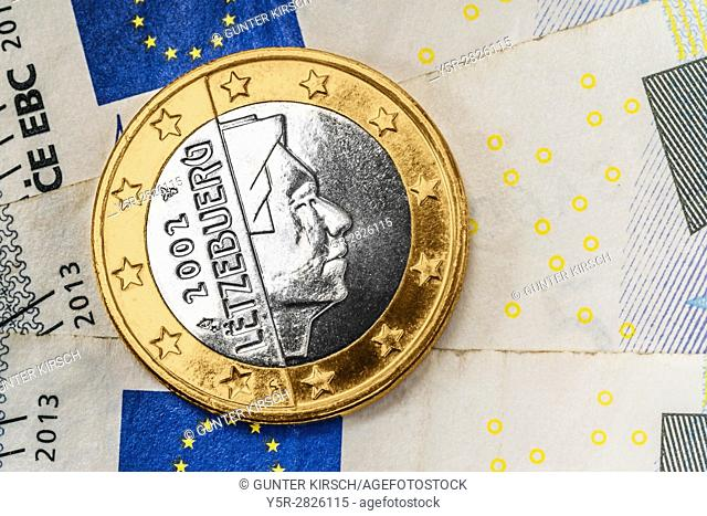 a 1 euro coin from Luxembourg on euro banknotes