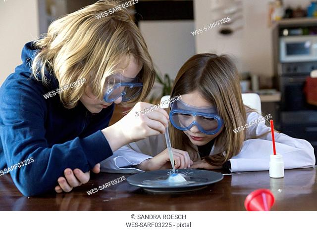 Two children wearing safety glasses using chemistry set at home
