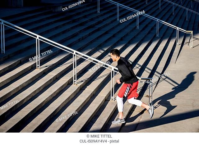 Young man training, running up city stairs