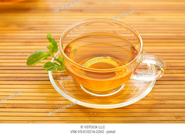 Tea in cup with mint leaf on saucer