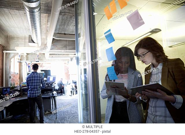 Businesswomen using digital tablets at conference room window