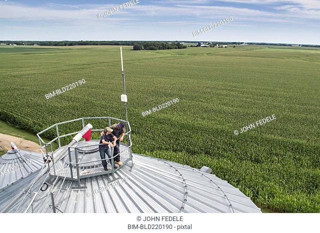 Caucasian farmer and son admiring farm from silo