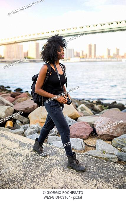 USA, New York City, Brooklyn, woman with camera walking at the waterfront