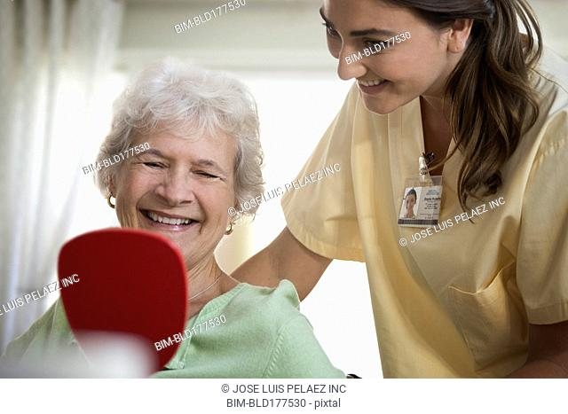 Caucasian nurse and patient using hand mirror