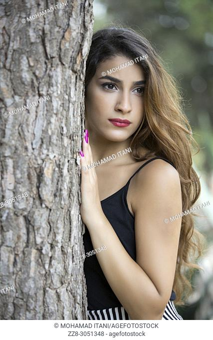 Beautiful young woman standing behind a tree looking away