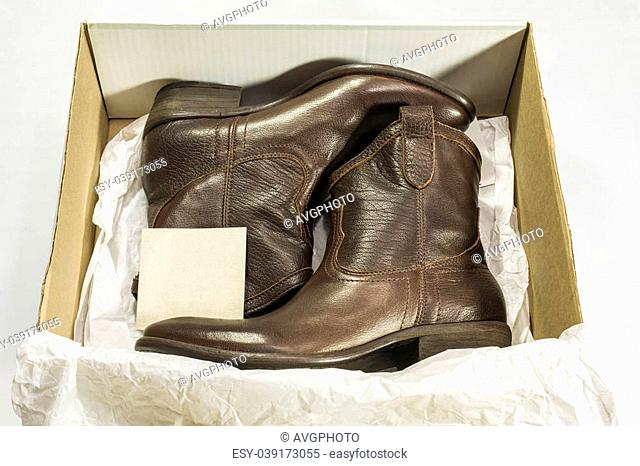 Open box with two brown leather cowboy boots inside (with tag)