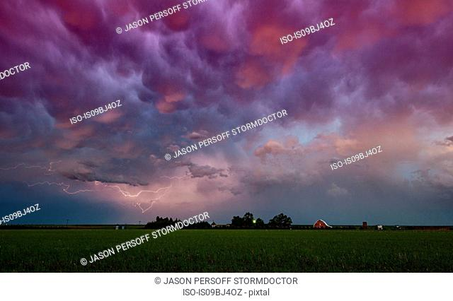 Lightning under storm cloud over farmhouse, Wray, Colorado, US