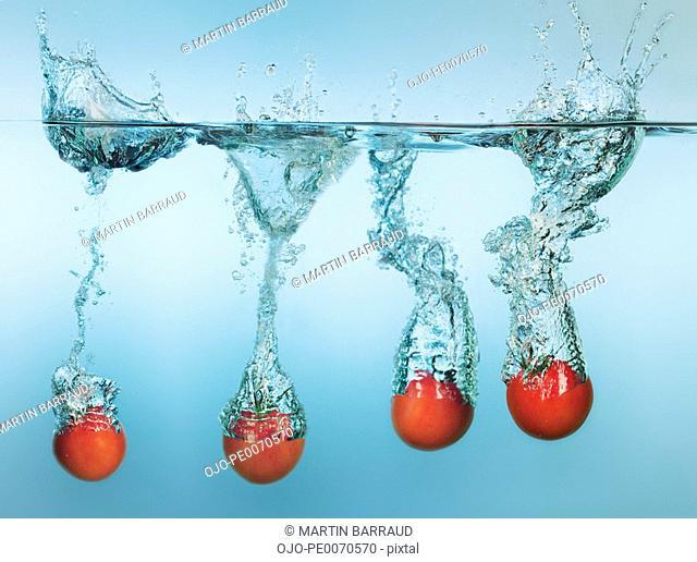 Tomatoes splashing in water