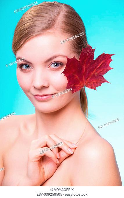 Skincare habits. Portrait of young woman with leaf as symbol of red capillary skin on turquoise. Face of girl taking care of her dry complexion