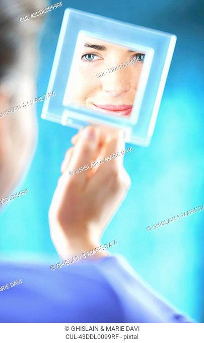 Woman examining herself in mirror
