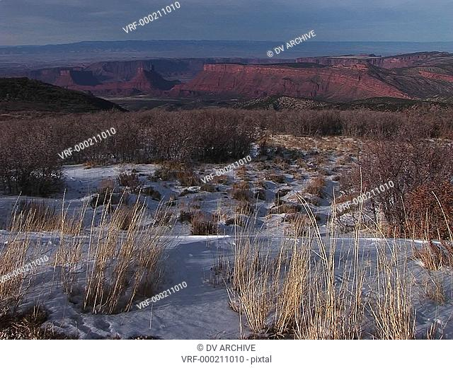 The desert southwest with distant buttes and snow in the foreground