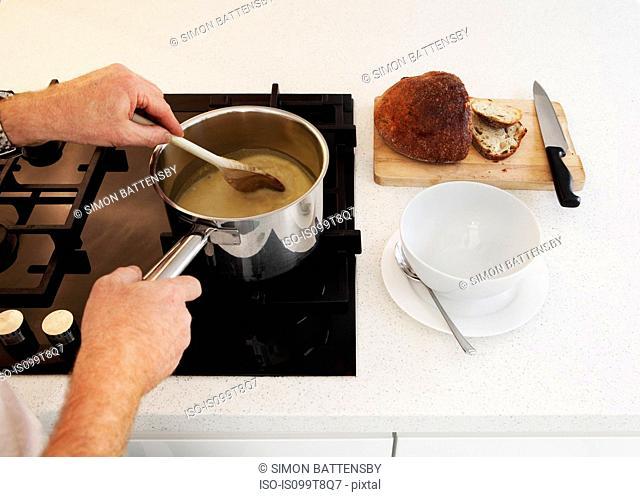 Man stirring saucepan of soup on hob