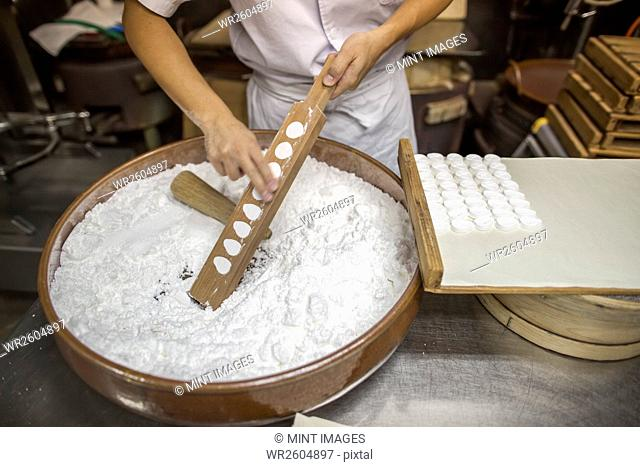 A small artisan producer of wagashi. A woman chef mixing a large bowl of ingredients and pressing the mixed dough into moulds in a commercial kitchen