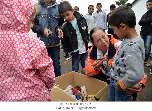 Volunteer camp manager Beatrix Hermann distributes toys to children in a camp tent set up by the refugee reception facility inIngelheim