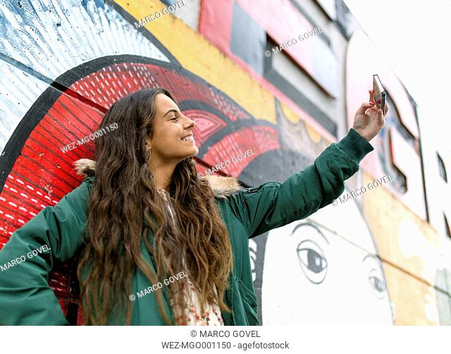 Smiling young woman taking a selfie at mural