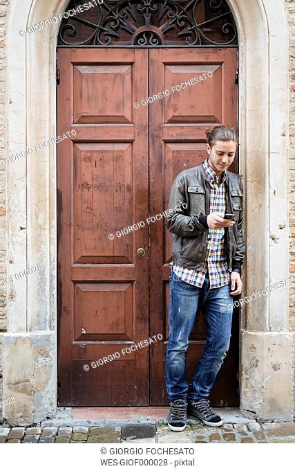 Italy, San Gimignano, young man in front of entrance door using his smartphone