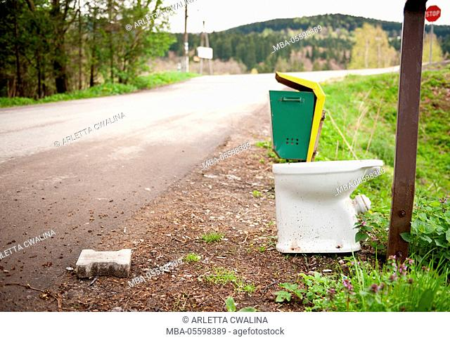 Old used toilette roadside garbage thrown away, lavatory standing exposed near rubbish bin, Poland, Europe, Trees and road behind toilet, nobody