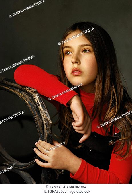 Close up of young female youth wearing red sweater sitting on old chair looking up