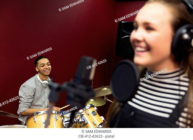 Smiling teenage musicians recording music, signing and playing drums in sound booth