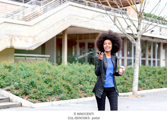 Young woman with afro hair in city, walking and talking to smartphone