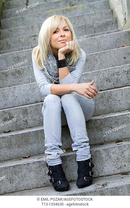 Seated on a stone stairway young woman