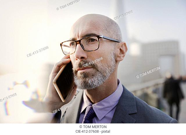 Close up serious businessman talking on cell phone