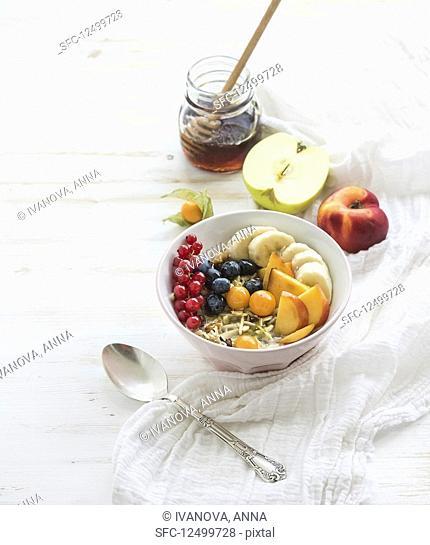 Bowl of oat granola with yogurt, fresh berries, fruit and honey