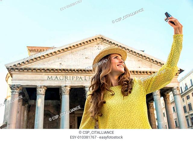 Happy young woman making selfie in front of pantheon in rome, it
