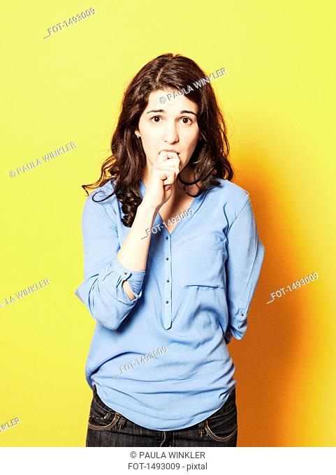Portrait of nervous young woman biting nails against yellow background