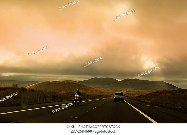 A motorcyclist and a car on a lonely road as a storm approaches, the Big Island, Hawaii, USA