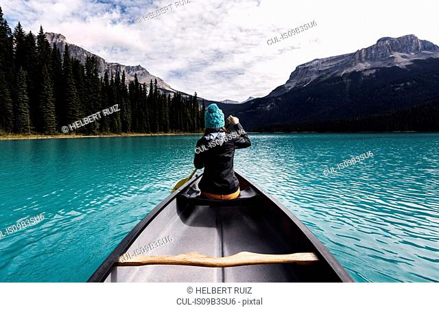 Young woman canoeing, rear view, Emerald Lake, Yoho National Park, Canada
