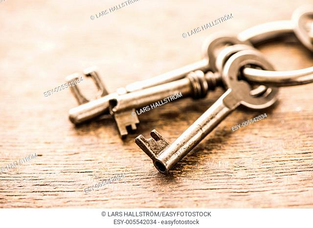 Close-up of a group of antique skeleton keys on wooden background