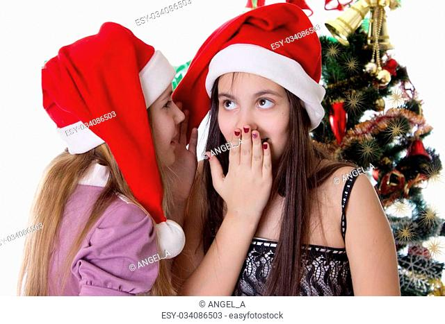 Two eleven years old girls sharing each other secrets on Christmas Eve