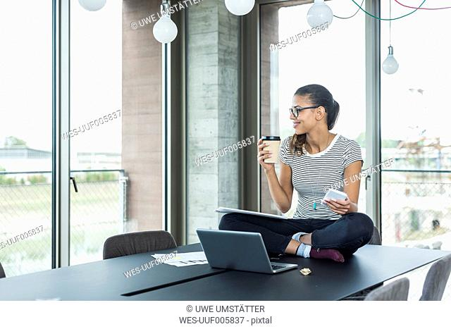 Smiling young woman sitting on conference table with laptop
