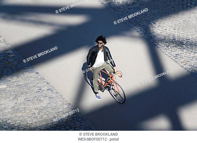 Elevated view of smiling man with sunglasses on bicycle