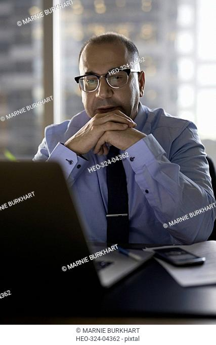 Focused male lawyer working late at laptop