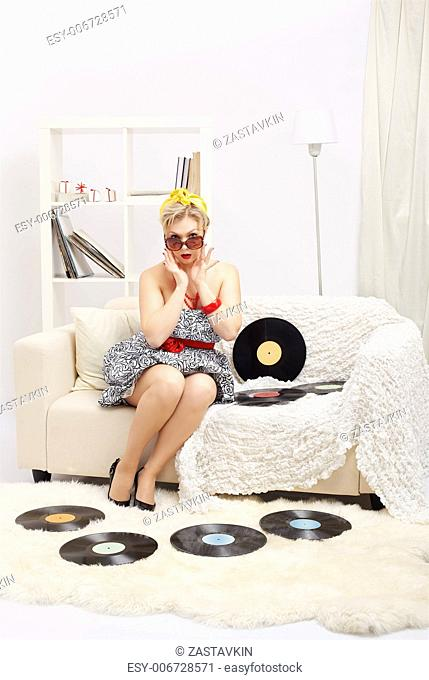 indoor portrait of beautiful surprised young blonde size plus woman model sitting on sofa with vinyl records in interior
