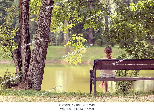 Russia, Saint Petersburg, back view of woman sitting on a bench looking at water in Shuvalovsky Park