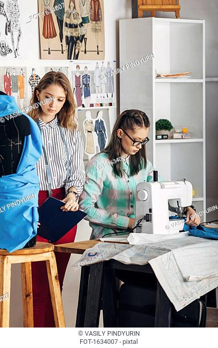 Beautiful assistant standing by female designer working on sewing machine at studio